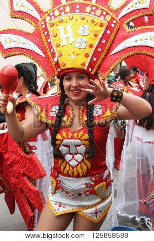 Cajamarca Peru - February 7 2016: Pretty young Peruvian woman in red and gold costume with maracas marches in Carnival parade in Cajamarca Peru on February 7 2016