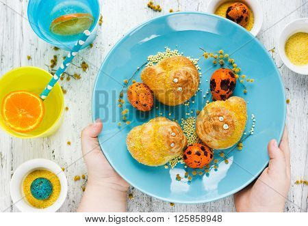 Traditional Easter bun in the shape of a bird. Easter baking composition festive sweet treats for kids top view