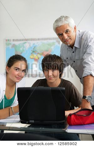 Portrait of a man and teenagers in front of a laptop computer in a classroom