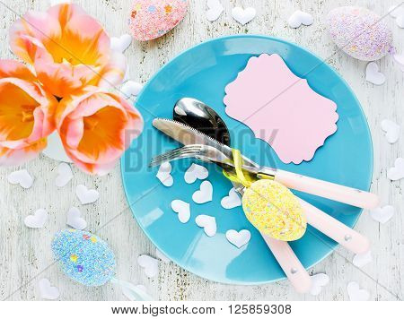 Easter table setting with Easter eggs tulips blank greeting card on white background top view