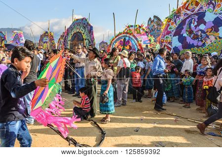 Sumpango, Guatemala - November 1 2015: Boy with homemade kite & visitors at giant kite festival on All Saints' Day to honor spirits of dead.