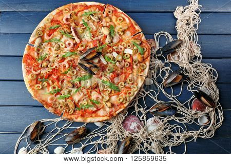 Pizza with seafood, red pepper and green olives on blue wooden table