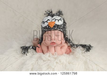 Three week old newborn baby boy wearing a crocheted owl hat. He's in a cute curled up chin on hands pose and sleeping on a white flokati rug.