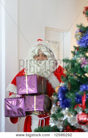 Santa Claus bringing gifts near a Christmas tree