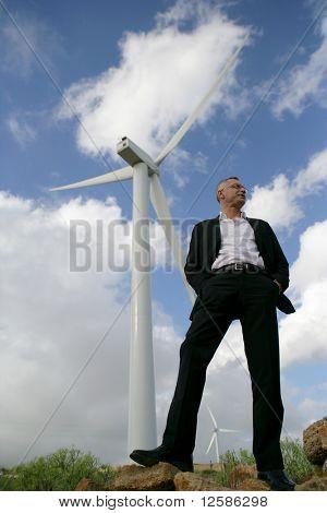 Mann in Anzug vor einer Windkraftanlage, Wegsehen