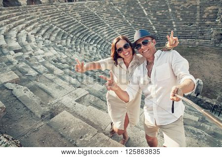 Couple in love take a selfie photo in ancient amphitheater