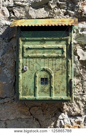 Detail of an Italian rusty metallic mailbox hanging on a wall. Portovenere Liguria Italy