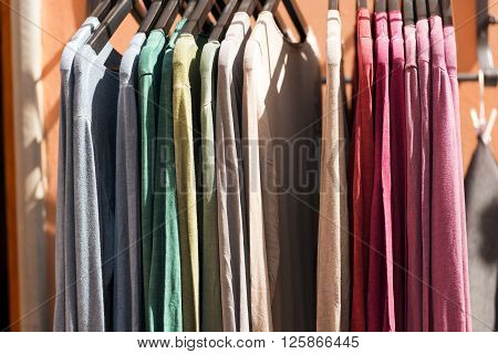 Detail of t-shirts on hangers in a street market in Italy