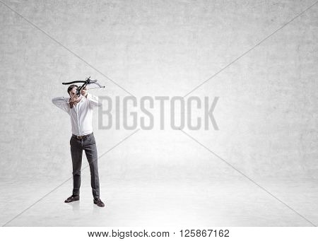 Businessman aiming at target with bow and arrow on concrete wall background. Mock up