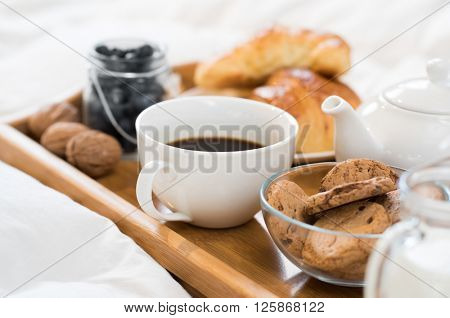 Breakfast in bed with hot coffee and croissants. Healthy breakfast kept on bed. Close up of a cup of tea with cookies on wooden tray in bed.