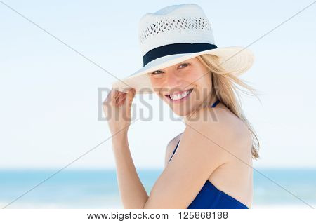 Woman wearing a straw hat and smiling. Portrait of a happy young woman in blue bikini with panama hat looking at camera with copy space.