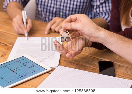Happy young couple getting keys of their new house. Closeup of the hand of a real estate agent who give the house keys to a woman while her boyfriend signing a contract.