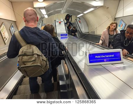 LONDON - APRIL 15: Commuters on the London Underground descend and ascend the escalators on April 15, 2016 in Shepherds Bush, London, UK.