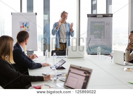 Business man clapping hands after successful meeting  in modern office.