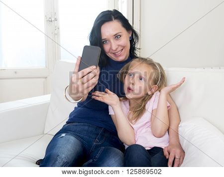 young happy woman with her little cute blond daughter taking selfie photo with mobile phone enjoying together at home sofa couch in mother and little girl self portrait picture concept