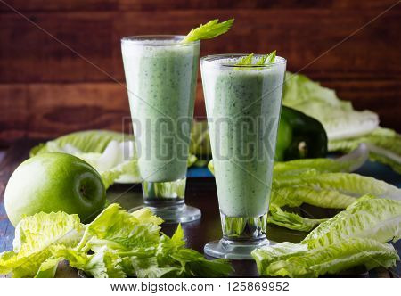 Two glasses of green smoothie and fresh green vegetables and fruits on black background