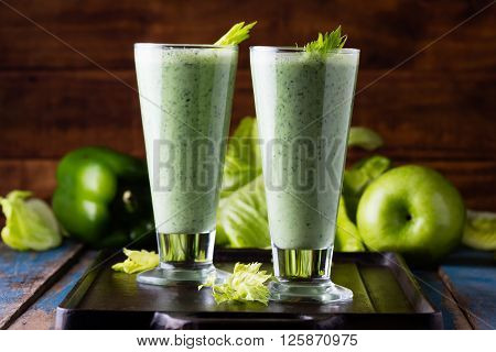 Two glasses of green smoothie and fresh green vegetables and fruits on wooden blue background