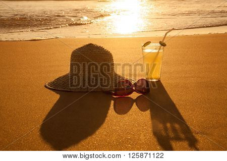Cold drink with straw hat and sunglasses on the beach on a hot summer day