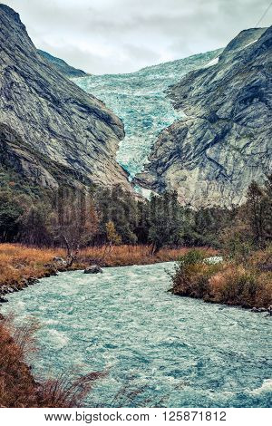 Briksdalsbreen glacier in Norway at autumn season. Mountain river from melted ice on foreground.