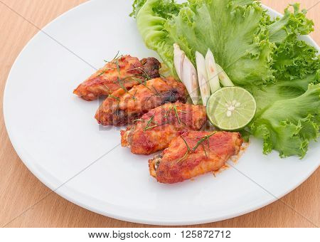 Chicken wings with cayenne pepper sauce on white plate.