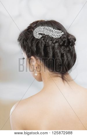 Beautiful fashionable brunette's head with jewelry .