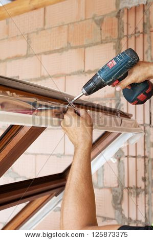Plastic window installation. Worker attaches anchor plate with screwdriver