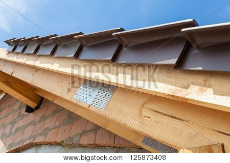Close-up view of roof detail with wooden rafters and roof tiles. New house under construction