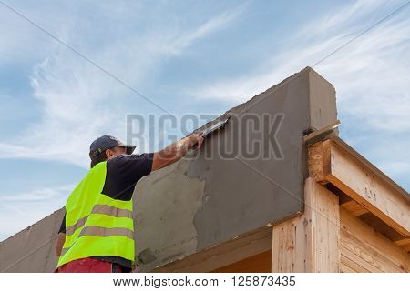 Construction worker with trowel plastering a facade of a new house