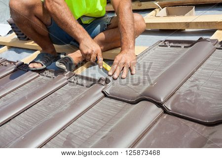 Hands of roofer laying tile on the roof. Installing natural red tile.