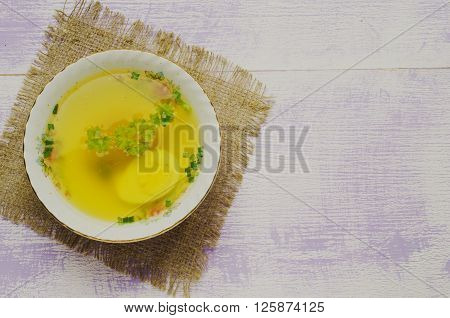 Broth With Vegetables In Plate On Wooden Table .