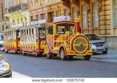 Lviv Ukraine - July 5 2014: Tourist tram with passengers in historical city center. Lviv Ukraine