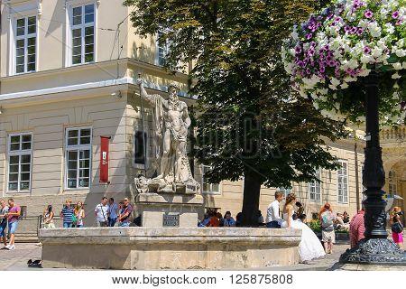 Lviv Ukraine - July 5 2014: People near Neptune fountain in historic city centre (Rynok Square)