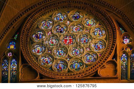 TOLEDO, SPAIN -  MAY 16, 2014 Rose Window Jesus Christ Saints Disciples Mary Stained Glass Cathedral Spanish Flag Toledo Spain. Cathedral started in 1226 finished 1493