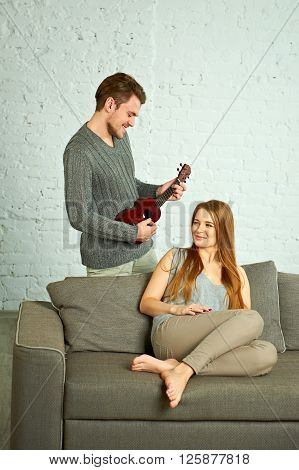 Young man playing ukulele. Beautiful woman listening in living room.