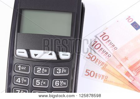 Payment terminal credit card reader and currencies euro money ,choice between cashless and cash paying for shopping finance concept