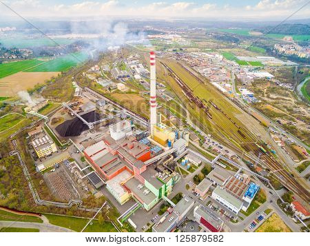 Modern combined heat and power plant from above. Fuming chimney with sulphur removal unit. Aerial view of heavy industry.