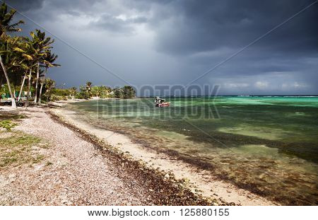 Beautiful Caribbean beach with palms, dark clouds and boats in bay, La Desirade, Guadeloupe, French West Indies