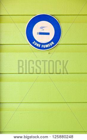Designated smoking area - blue cardboard on green wooden background