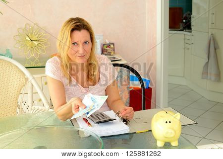 blond woman calculate housekeeping allowance in living room