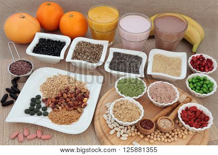 Body building high protein food with supplement powders, vitamin pills, protein and fruit smoothie shakes, grains, seeds, nuts, vegetables and fruits.