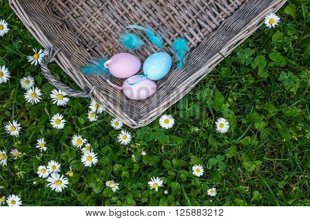 Top View Of Painted Eggs In Basket Against Fresh Flowers Background