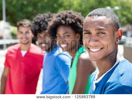 Group of african american and latin young adults laughing at camera in city