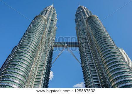 KUALA LUMPUR MALAYSIA - FEBRUARY 29: Petronas twin towers on February 29 2016 in Kuala Lumpur Malaysia. The famous landmarks of Malaysia with blue sky.