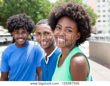 African american woman with two friends laughing at camera in the city