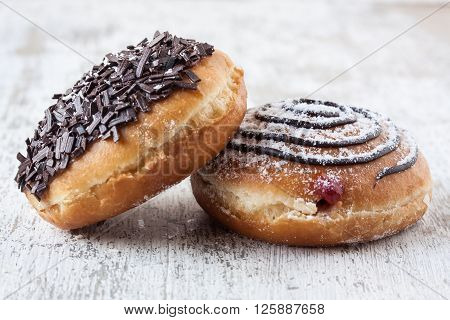 donuts with chocolate and marmalade on a white wooden background