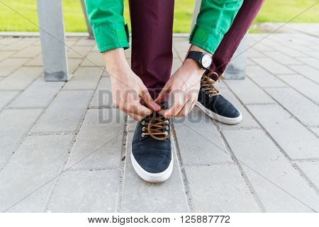 people, footwear and fashion concept - close up of male hands tying shoe laces on street