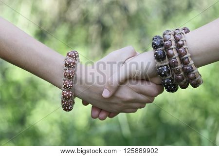 Young womens handshake teenagers handshake in green nature background. Two hands together with boho style jewelry boho-chic.
