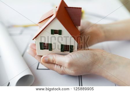 architecture, building, construction, real estate and people concept - close up of architect hands holding living house model above blueprint on table