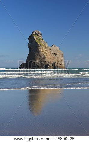 Island at Wharariki Beach New Zealand. Rock formation at the West Coast of the South Island. Famous tourist attraction.