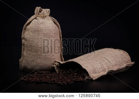 Coffee bags burlap with coffee beans scattered on black table. With black background and vygnete.